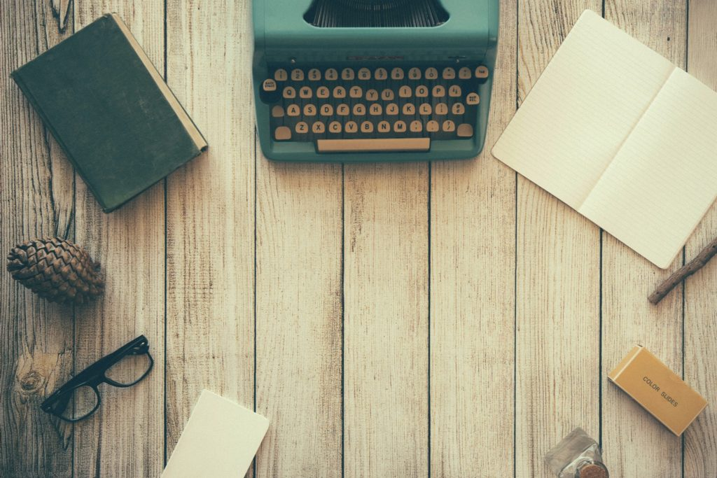 vanha kirjoituskone ja paperia pöydällä